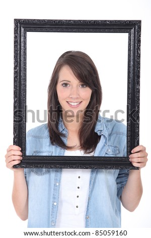 Woman holding up a picture frame - stock photo