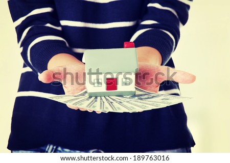 Woman holding US dollars bills and house model  - real estate loan concept - stock photo