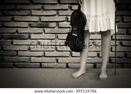 woman holding violin with old dirty brick wall background