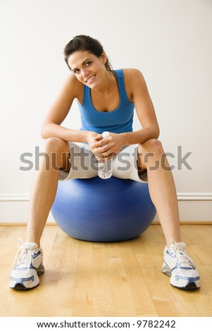 Woman holding water bottle sitting on balance ball at gym smiling. - stock photo