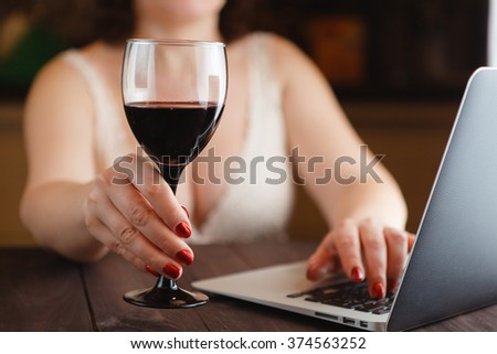 woman holding wine glass while working laptop at night