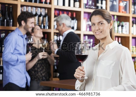 Woman Holding Wineglass While Friends Communicating In Backgroun