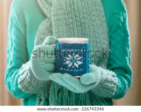 Woman holding winter cup close up on light background. Woman hands in teal gloves holding a cozy mug with hot cocoa, tea or coffee and a candy cane. Winter and Christmas time concept.  - stock photo