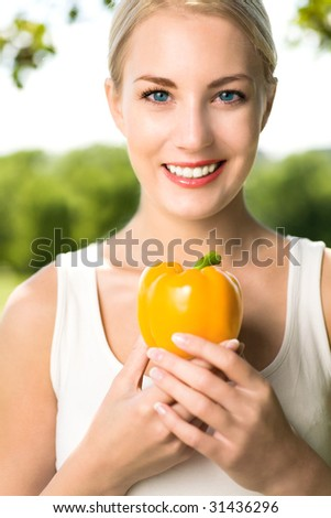 Woman holding yellow pepper