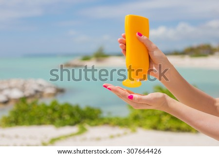 Woman holding yellow sunscreen bottle in hands - stock photo