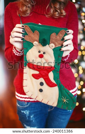 Woman holds a christmas socks with presents in decorated room - stock photo