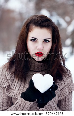 woman holds a heart of snow. The concept of Valentine's Day - stock photo