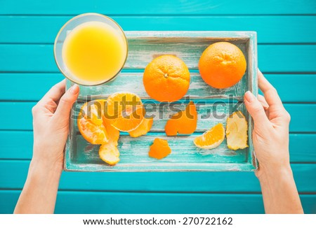 Woman holds a vintage tray with mandarins and fresh juice in her hands. Top view - stock photo
