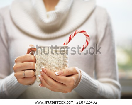 Woman holds a winter cup close up. Woman hands with elegant french manicure nails design holding a cozy knitted mug with cocoa, tea or coffee and a candy cane. Winter and Christmas time concept.  - stock photo