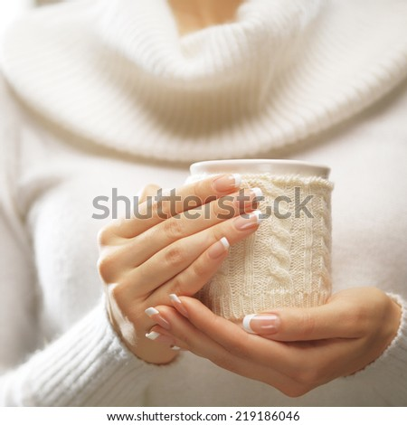 Woman holds a winter cup close up. Woman hands with elegant french manicure nails design holding a cozy knitted mug. Winter and Christmas time concept.  - stock photo
