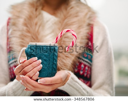Woman holds a winter cup close up. Woman hands with elegant french manicure nails design holding a cozy knitted mug with hot cocoa or coffee with a mint candy cane. Winter and Christmas time concept.  - stock photo