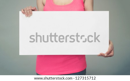 Woman holds an empty white board sign in both hands - stock photo