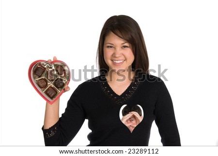 Woman holds box of valentines candy as her boyfriend searches for her heart - stock photo