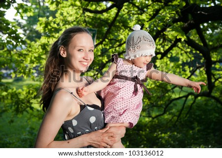 Woman holds child on the background of trees - stock photo