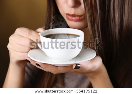 Woman holds cup of coffee and saucer in hands, close up