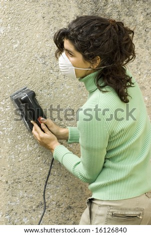 Woman holds electric sander while wearing mask. Vertically framed photo. - stock photo