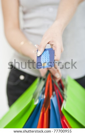 Woman holds gift bags and credit card - stock photo