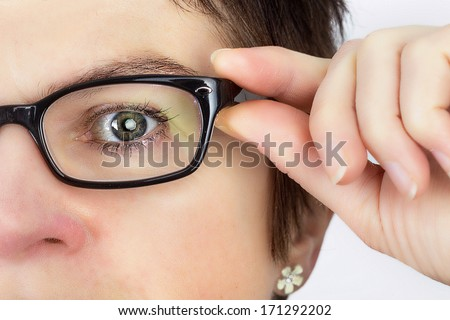 Woman holds her glasses