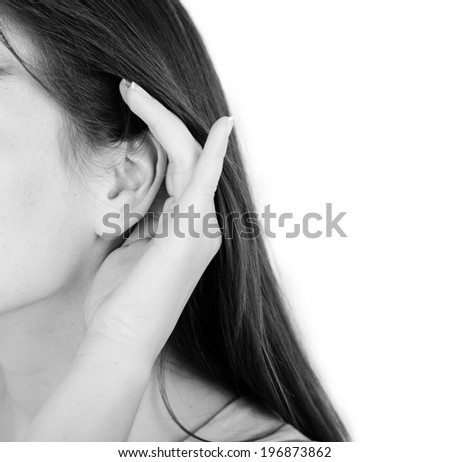 Woman holds her hand near ear and listens - stock photo