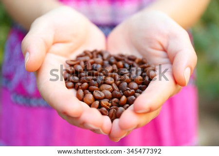 Woman holds in hands roasted coffee beans, heart shaped - stock photo