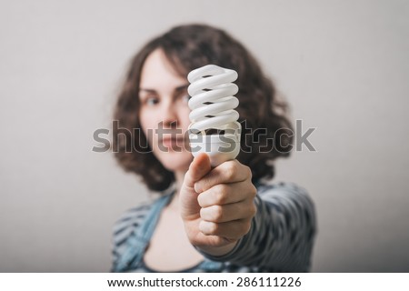 Woman holds in her hand new generation of light bulb - stock photo