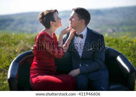 Woman holds man's chin while sitting on the black couch in the field