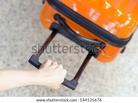 Woman holds orange suitcase in hand.