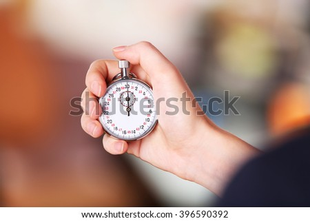 Woman holds stopwatch in hand, close up - stock photo