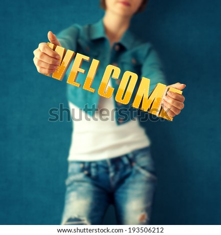 Woman holds word welcome on bright colorful background - stock photo