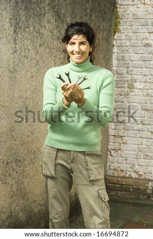 Woman holds wrenches in front of camera. She is smiling. Vertically framed photo. - stock photo