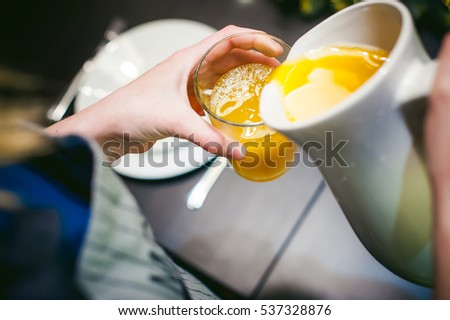 woman housewife setting table. young blonde in dress and apron, served in dining table, puts dishes, doing work in kitchen. pours orange juice yellow drinking, holding jug in his hands. Close-Up
