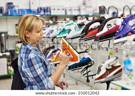 Woman housewife shopping for iron, smiling - stock photo