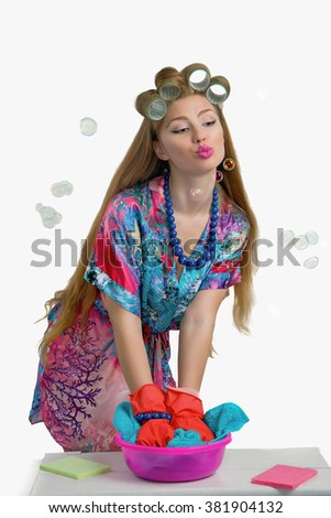 woman housewife wipes in the kitchen, in a bright robe and gloves on a white background with humor
