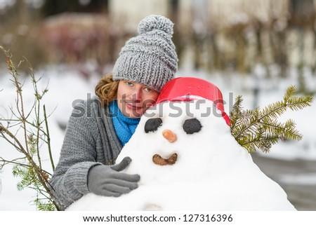 woman hugged a snowman - stock photo