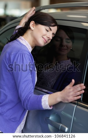 Woman hugging a car while closing her eyes - stock photo