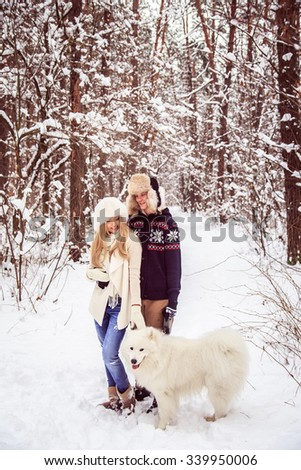 Woman hugging man standing in a winter forest, near white dog, kids winter hats in class