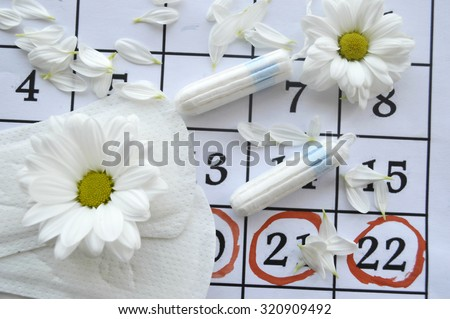 Woman hygiene protection, close-up.menstruation calendar with cotton tampons,daisy - stock photo