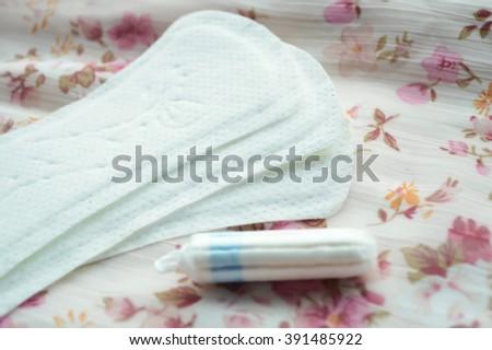 Woman hygiene protection, close-up.menstruation calendar with cotton tampons,pink rose, a symbol of femininity.female pearl necklace.feminine pads