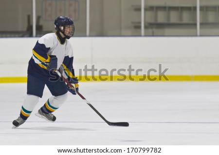 Woman ice hockey player during a game - stock photo