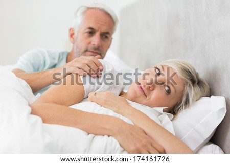 Woman ignoring mature man while lying in bed at the home