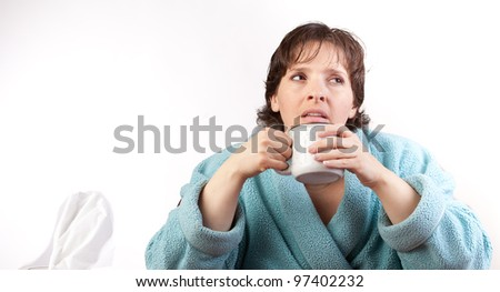 Woman in a bathroom with a bad cold holding a mug - stock photo