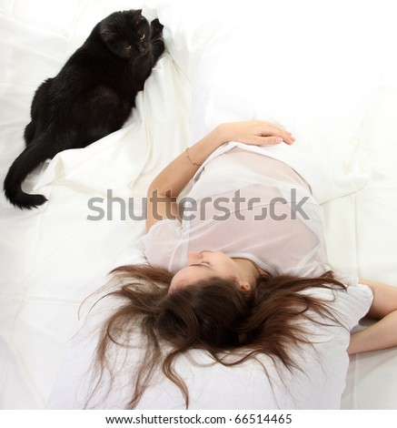 Woman in a bed with her black cat