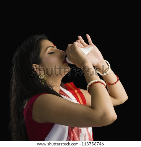 Woman in a Bengali sari blowing conch shell - stock photo