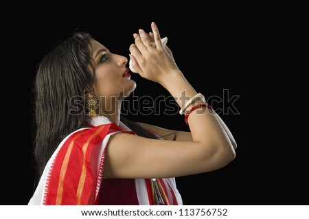 Woman in a Bengali sari blowing conch shell