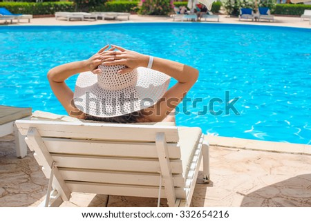 Woman in a big white hat relaxing on a lounger by the pool. - stock photo