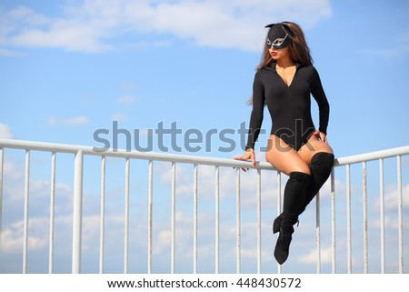 Woman in a black bodysuit and mask cat sitting on a metal railing on the roof - stock photo