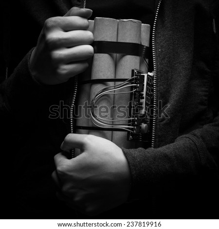 woman in a black jacket strapped with explosives and detonator holds in her hand - stock photo