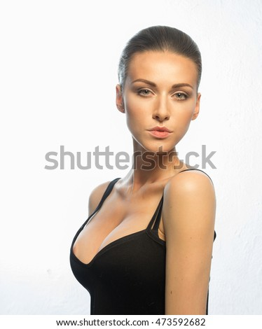 Woman in a black T-shirt, with a beautiful face and an attractive, large breasts