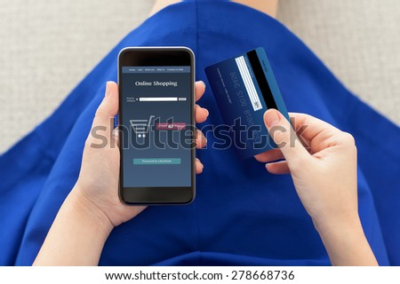 woman in a blue dress holding a phone with online shopping on the screen and credit card - stock photo
