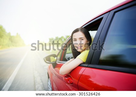 Woman in a car against the backdrop of receding into the distance the road. Motion effect. Travel concept. - stock photo